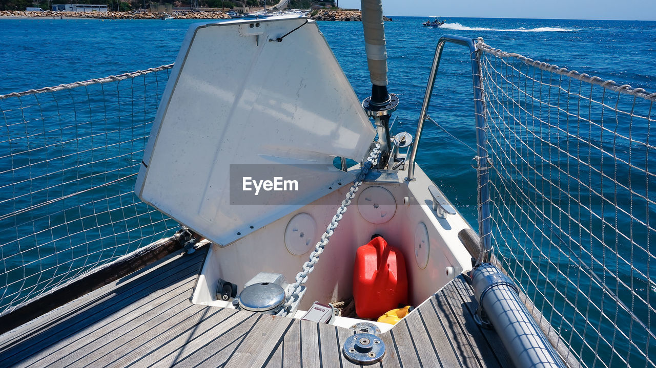 Opened anchor locker on sailing boat open sea, wooden deck