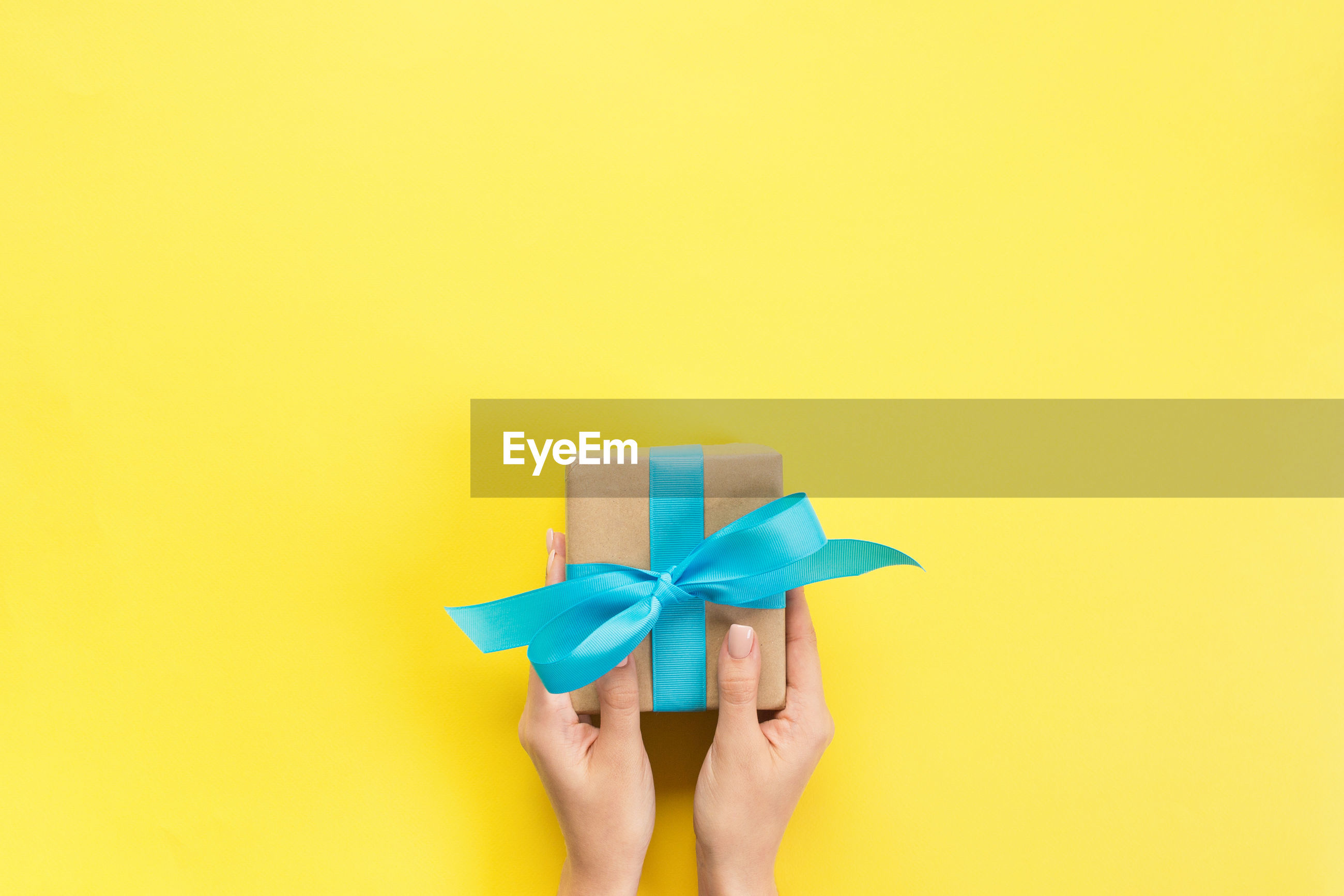 Cropped hands of woman holding wrapped gift box over yellow background