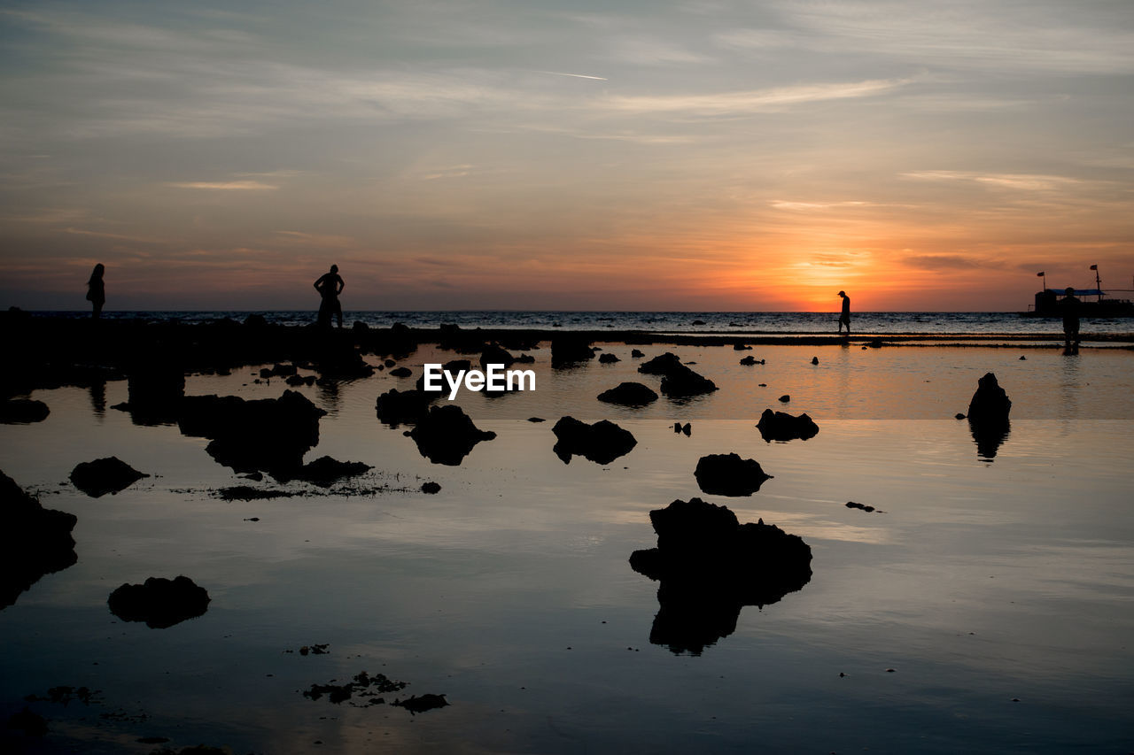 water, sky, sunset, sea, reflection, rock, beauty in nature, cloud - sky, rock - object, scenics - nature, solid, beach, land, tranquility, nature, silhouette, orange color, real people, tranquil scene, outdoors, horizon over water