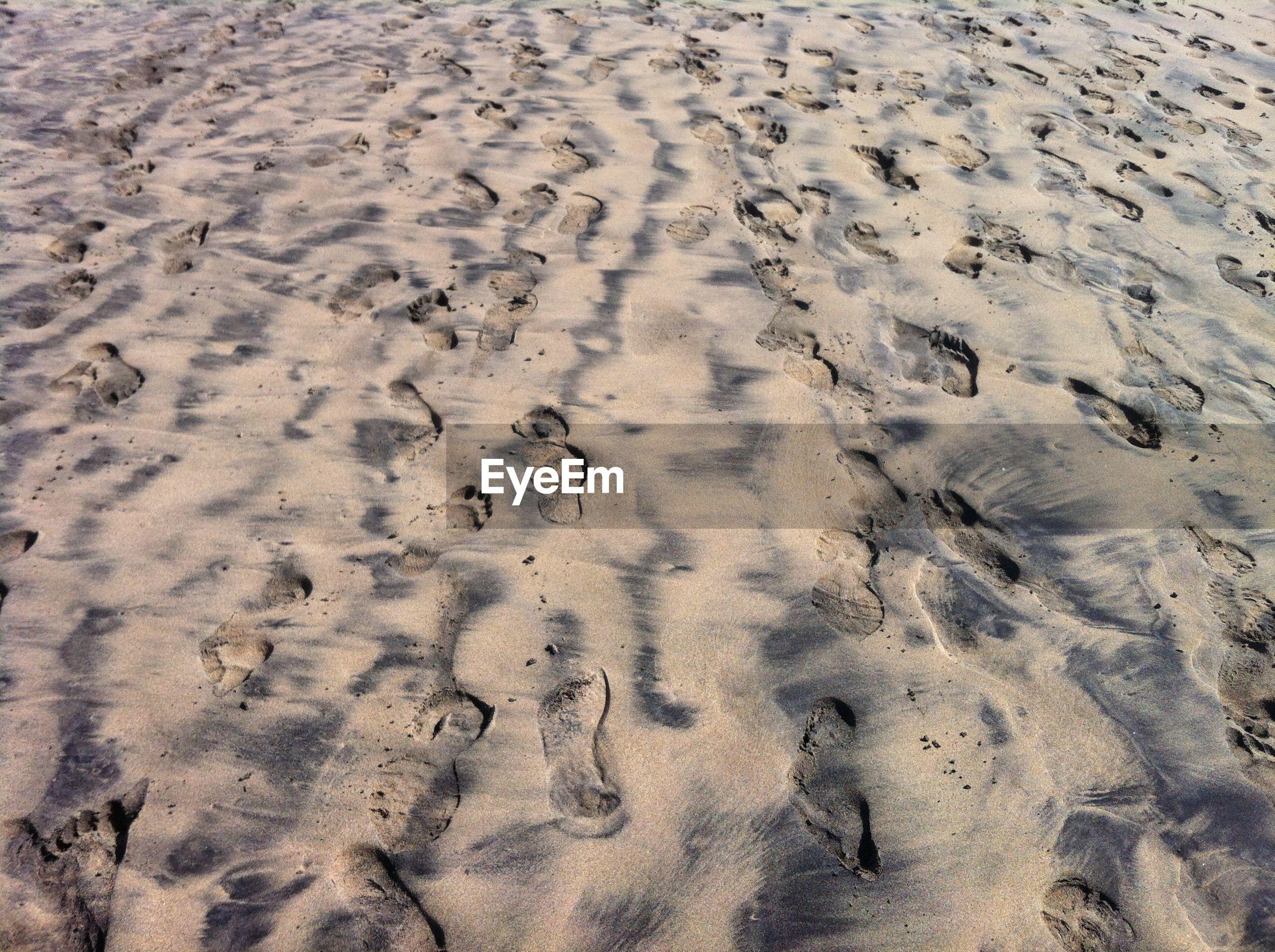 Full frame shot of footprints on sand at beach