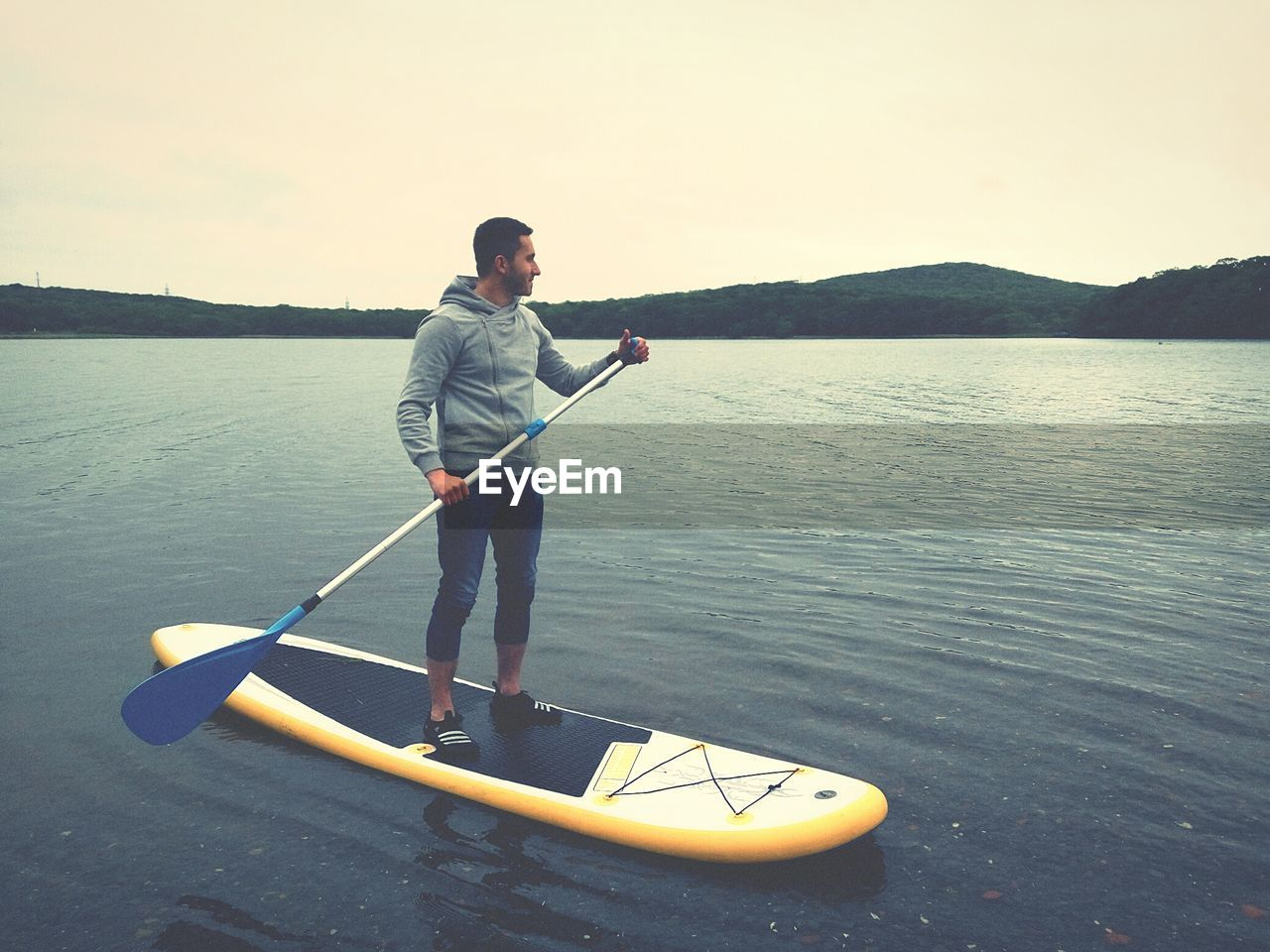 real people, one person, lifestyles, water, leisure activity, nature, standing, casual clothing, oar, outdoors, beauty in nature, day, full length, vacations, scenics, mountain, men, nautical vessel, young adult, paddleboarding, sky, adult, people