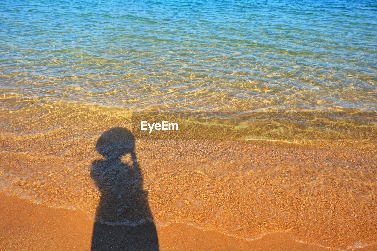 land, water, beach, nature, shadow, sand, sea, high angle view, sunlight, one person, day, focus on shadow, leisure activity, standing, beauty in nature, lifestyles, outdoors, real people