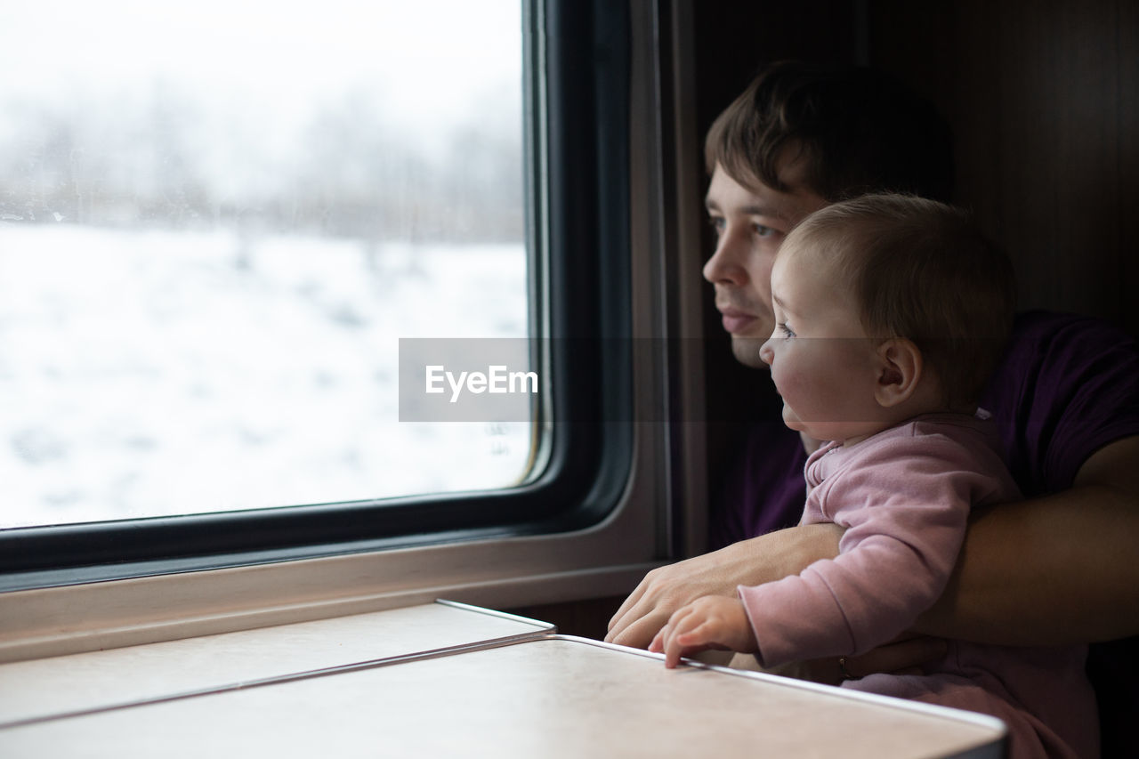 REAR VIEW OF PEOPLE LOOKING AT TRAIN WINDOW