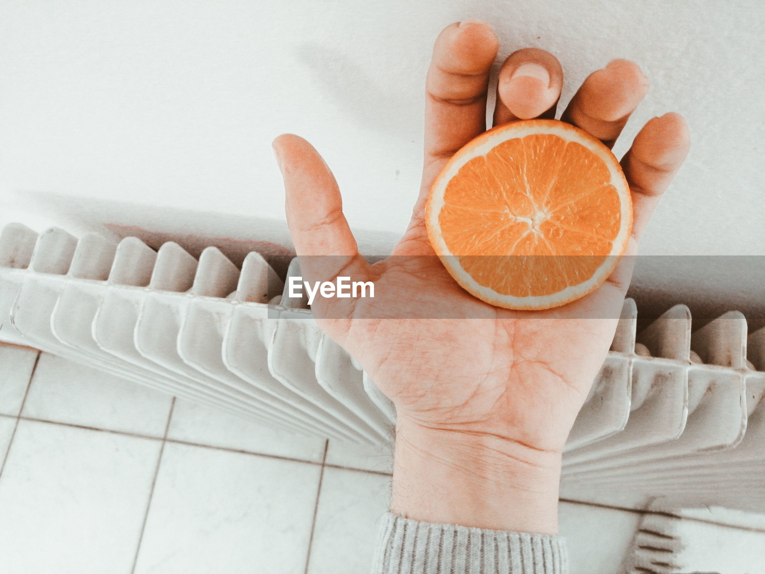 MIDSECTION OF MAN HOLDING ORANGE