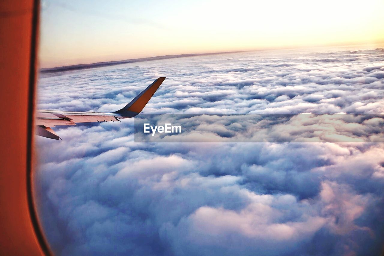 airplane, transportation, cloud - sky, sky, flying, mode of transport, sunset, air vehicle, mid-air, journey, sea, airplane wing, aircraft wing, nature, cloudscape, scenics, beauty in nature, aerial view, travel, no people, jet engine, outdoors, horizon over water, water, vehicle part, commercial airplane, day
