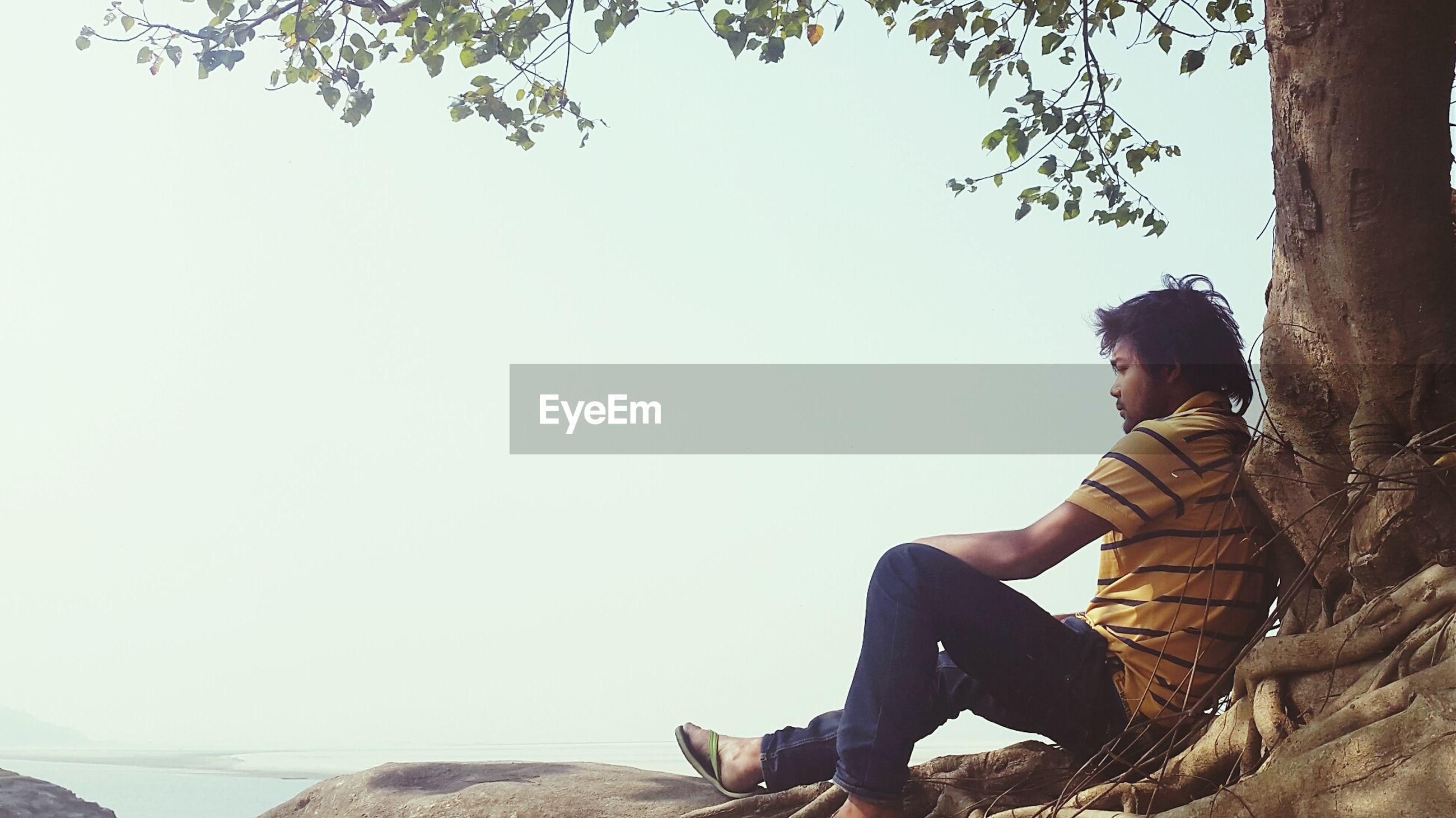 lifestyles, leisure activity, young adult, sitting, clear sky, young men, standing, casual clothing, men, relaxation, side view, three quarter length, waist up, full length, copy space, person