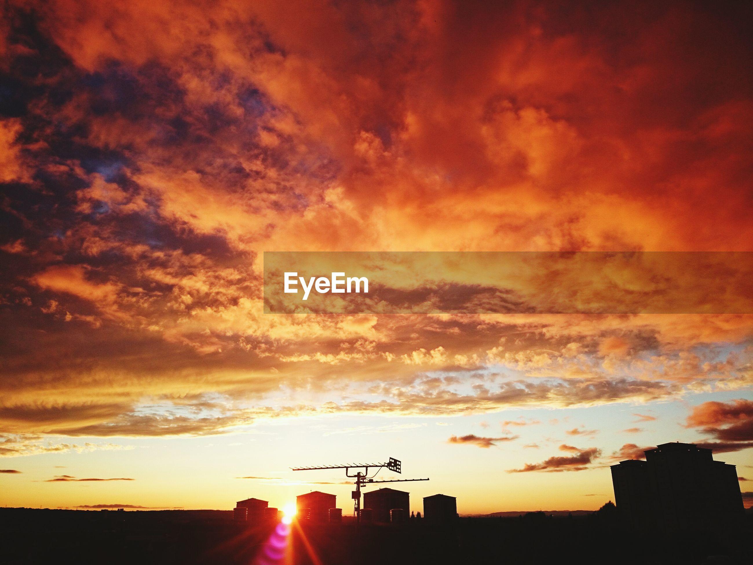 sunset, sky, cloud - sky, orange color, sun, silhouette, beauty in nature, scenics, dramatic sky, cloudy, sunbeam, building exterior, sunlight, built structure, cloud, nature, architecture, idyllic, tranquil scene, weather