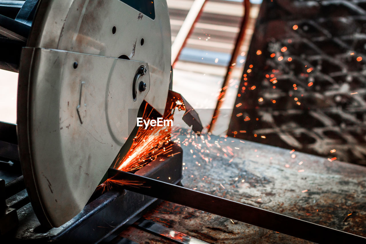 Close-Up Of Electric Saw Cutting Metal In Factory