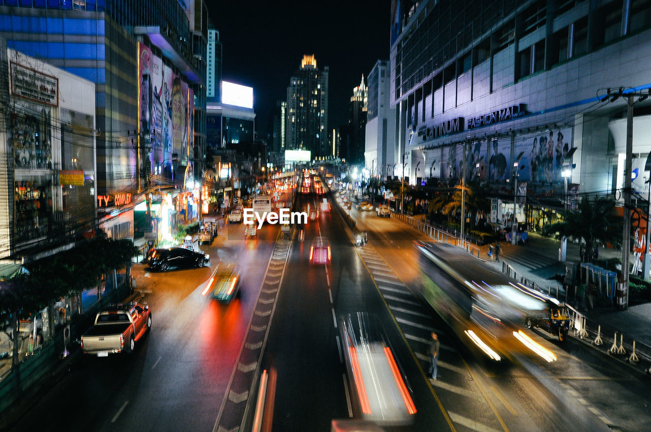 building exterior, architecture, motion, city, illuminated, blurred motion, night, built structure, transportation, long exposure, road, car, city life, street, speed, outdoors, high street, no people
