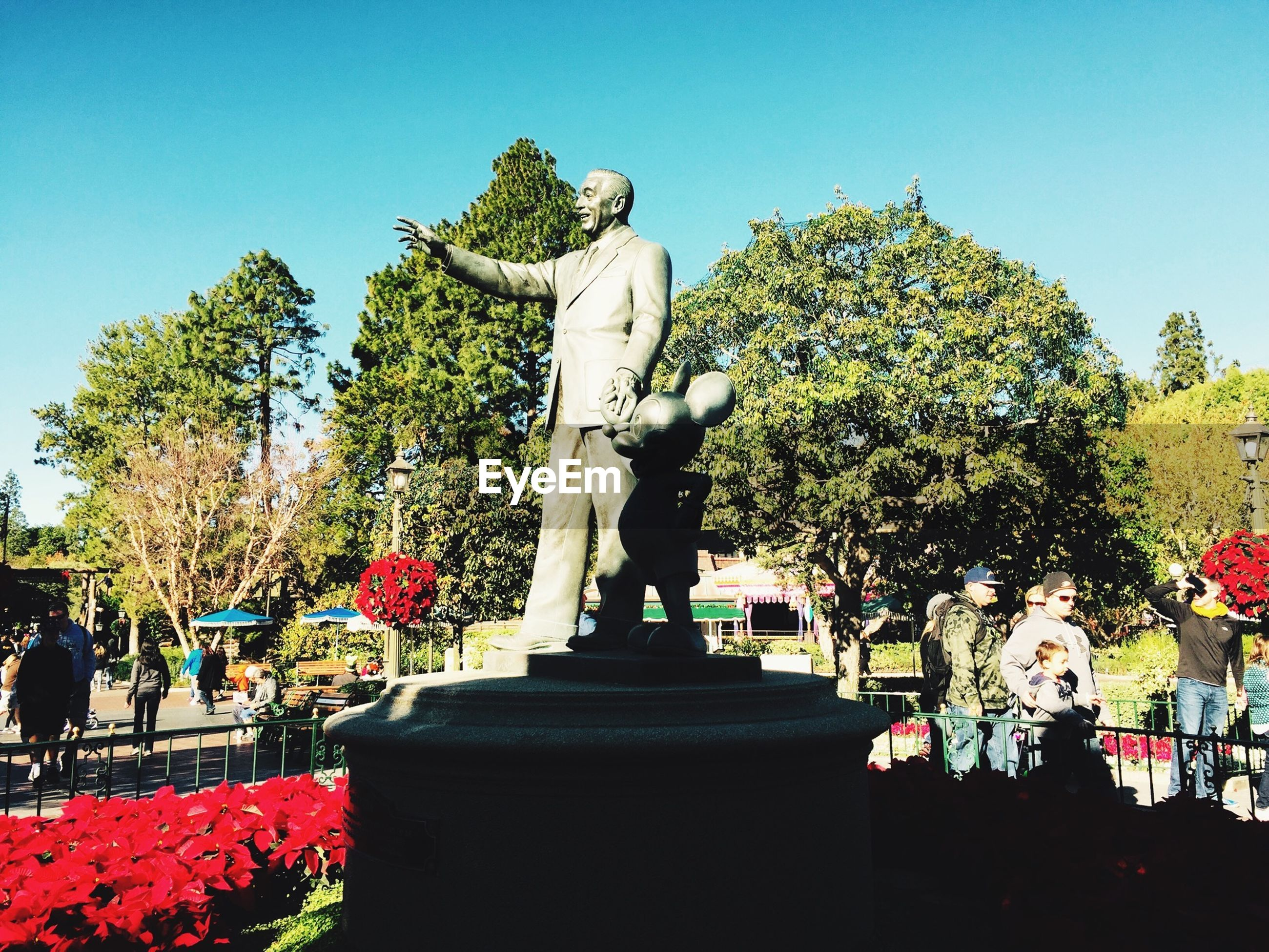 tree, clear sky, statue, sculpture, human representation, art, flower, art and craft, growth, creativity, park - man made space, plant, nature, sky, religion, sunlight, day, outdoors, spirituality