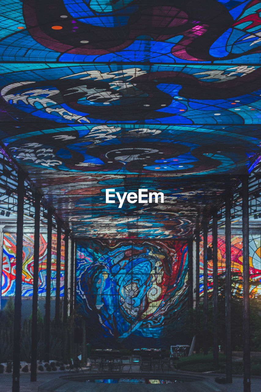 architecture, built structure, multi colored, no people, creativity, graffiti, indoors, art and craft, illuminated, blue, pattern, metal, building, day, connection, lighting equipment, place of worship, architectural column, ceiling