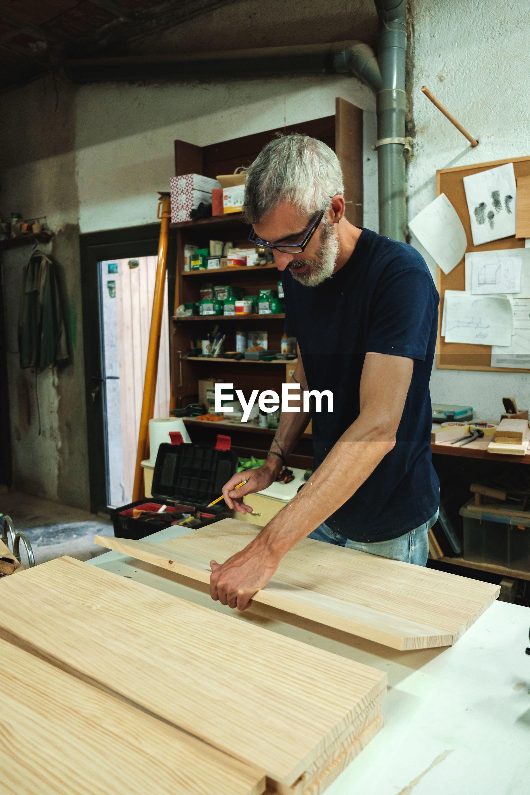 Craftsman working on wooden planks in workshop
