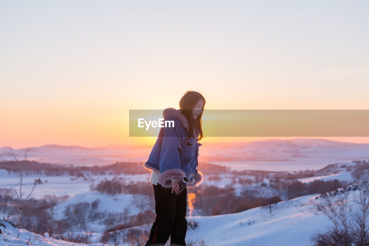 WOMAN STANDING ON SNOW DURING WINTER AGAINST SKY