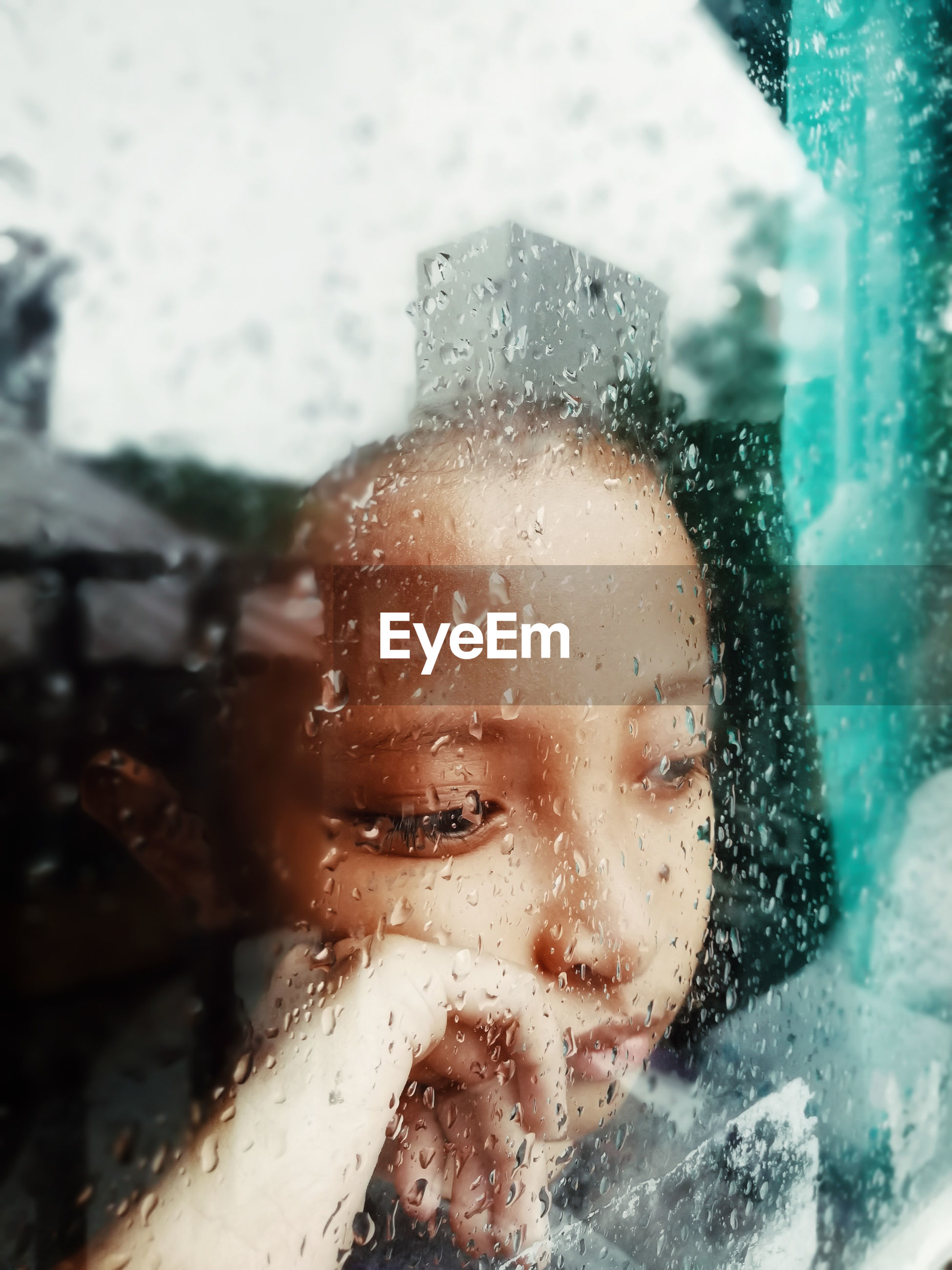 Thoughtful girl seen through wet glass window