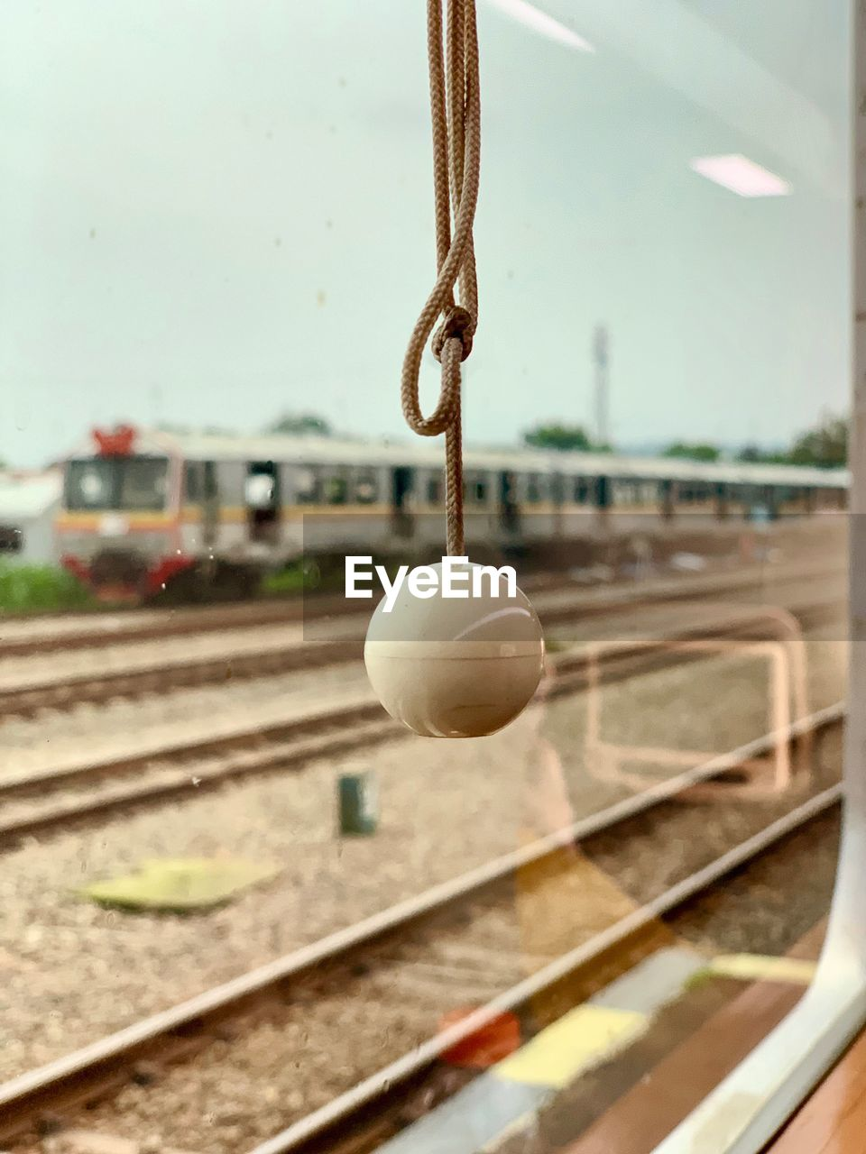 focus on foreground, rail transportation, mode of transportation, track, railroad track, no people, transportation, day, close-up, hanging, vehicle interior, window, train, outdoors, ball, glass - material, public transportation, car, sport