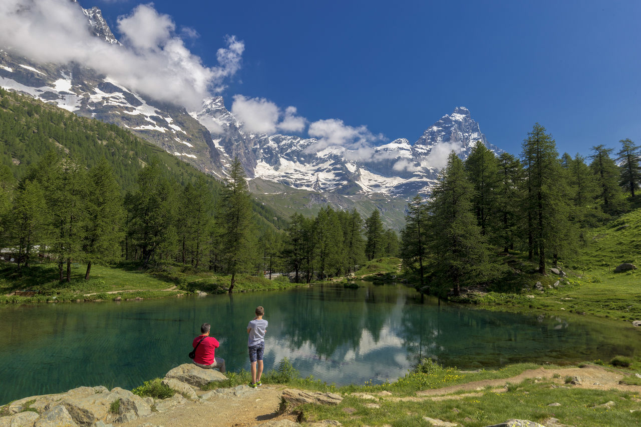 water, lake, tree, beauty in nature, scenics - nature, mountain, leisure activity, plant, sky, two people, togetherness, women, nature, real people, adult, men, day, tranquility, non-urban scene, mountain range
