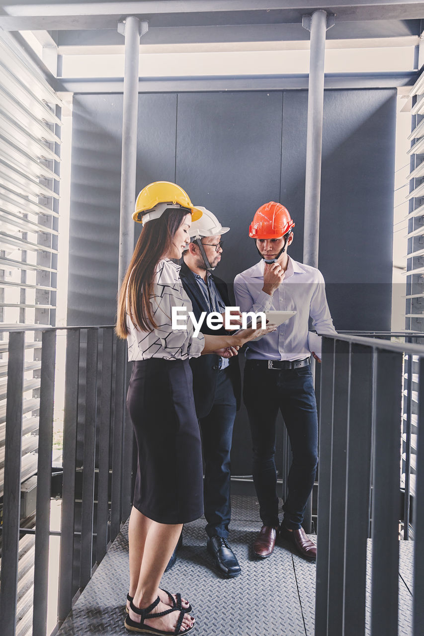 helmet, occupation, real people, headwear, hardhat, architecture, women, standing, adult, business, people, built structure, communication, hat, cooperation, men, industry, protection, engineering, design professional, architect, teamwork, coworker