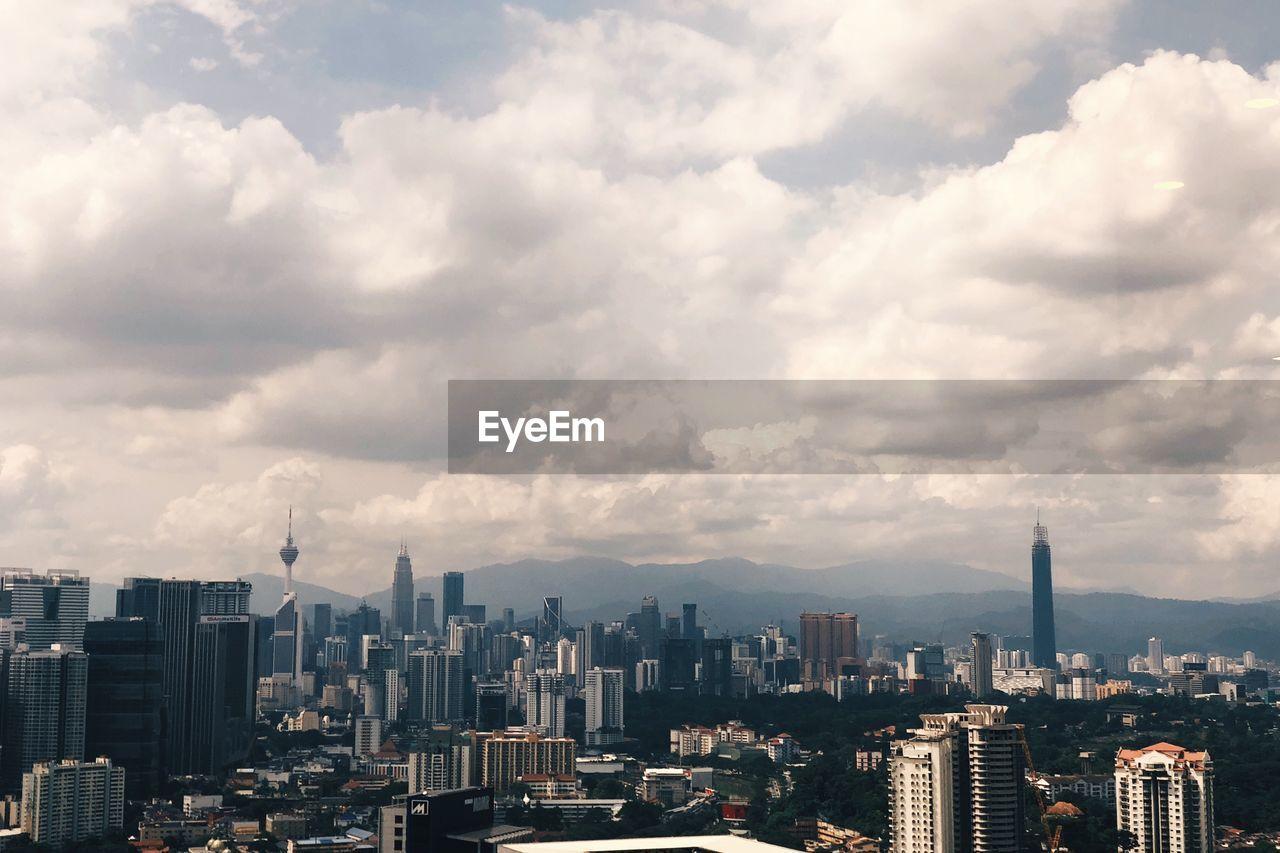 Aerial View Of Modern Buildings Against Cloudy Sky In City