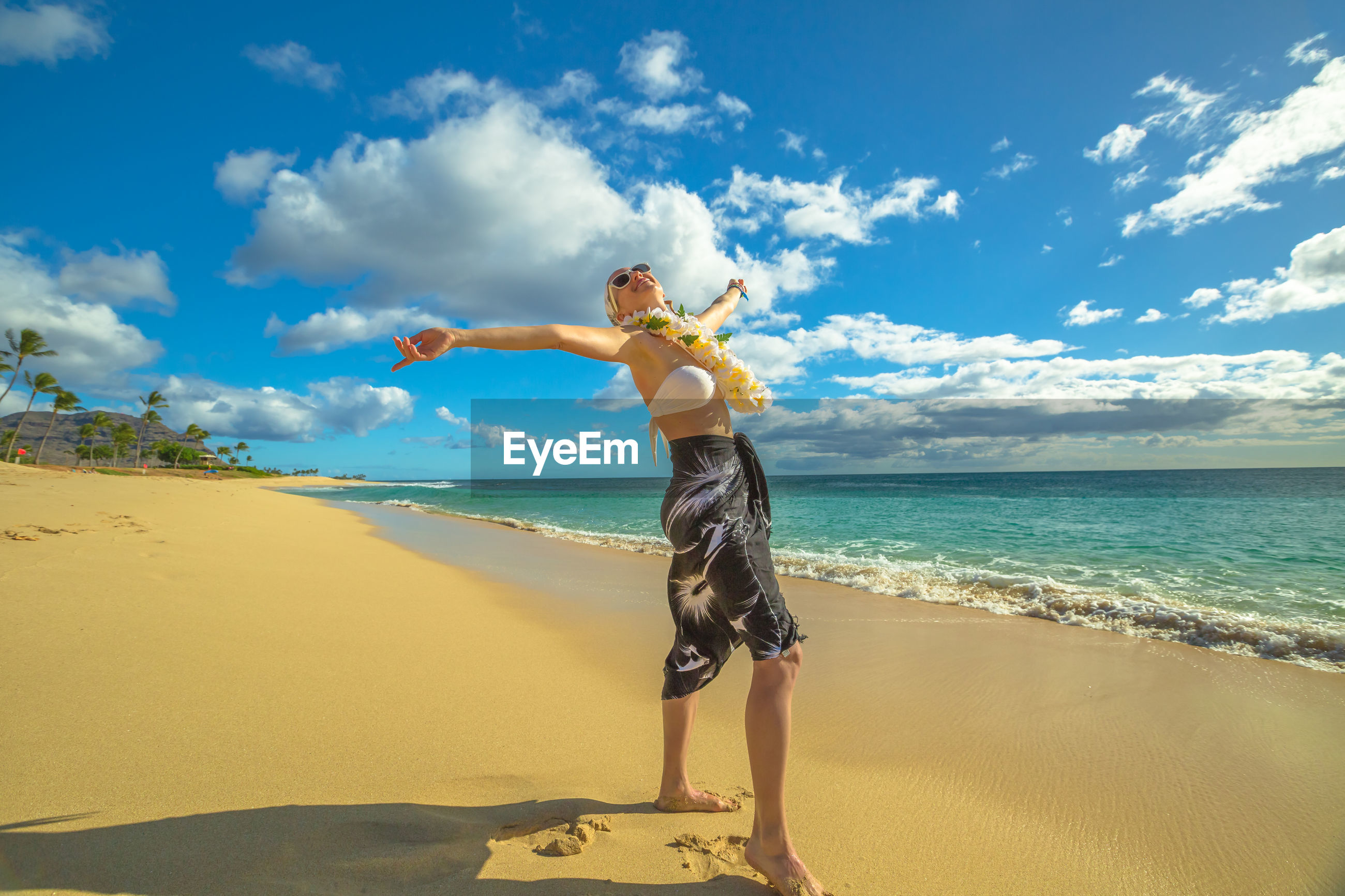 Mature woman wearing floral garland while standing with arms outstretched at beach against sky