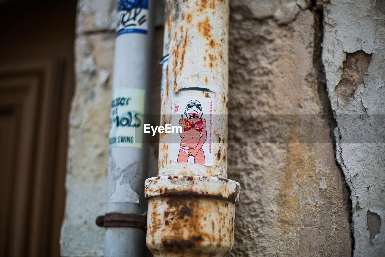 Sticker showing obscene gesture on rusty metallic pipe against wall