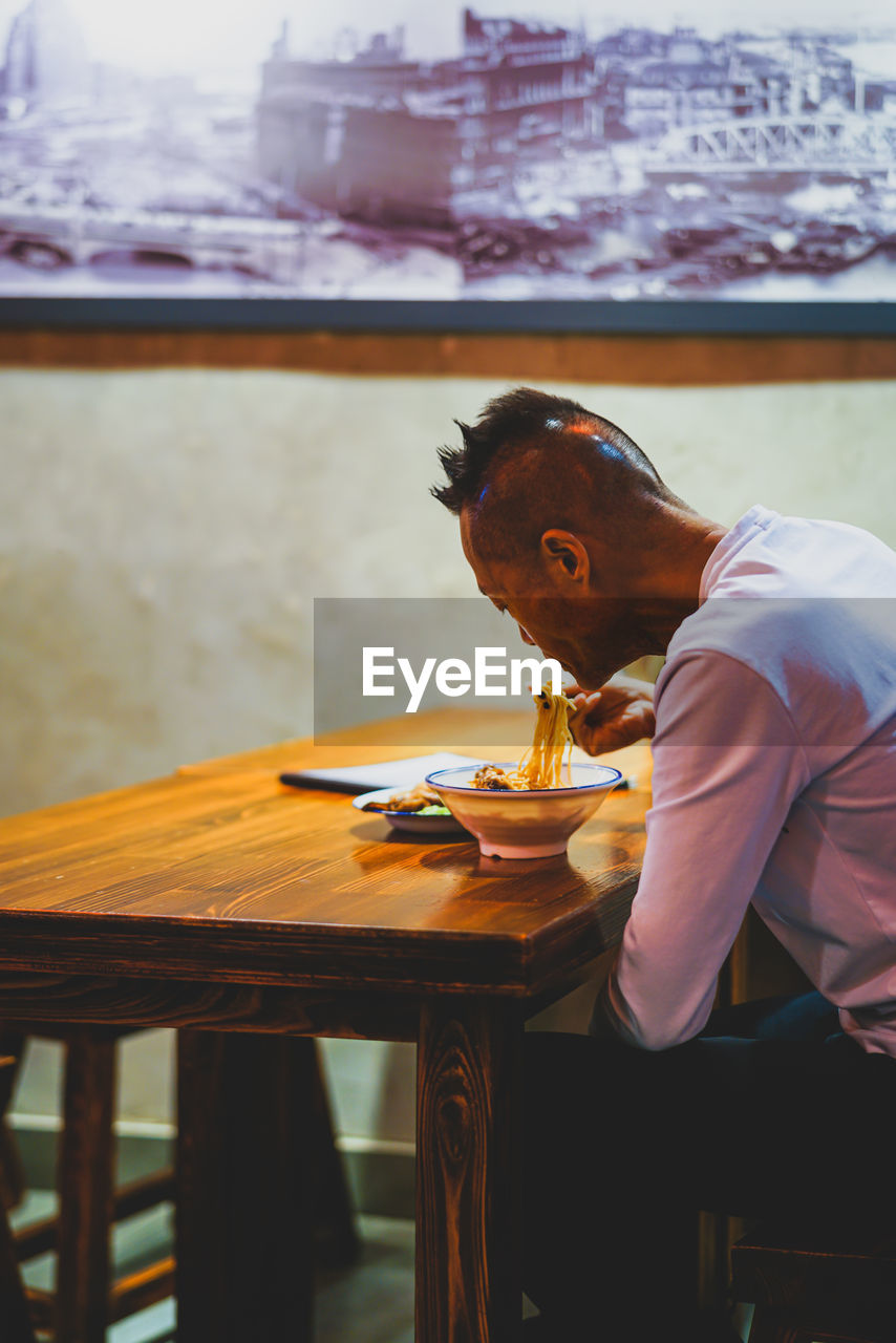 real people, table, one person, sitting, young adult, casual clothing, three quarter length, lifestyles, focus on foreground, leisure activity, young men, mid adult, business, men, looking, side view, seat, technology, contemplation, hairstyle