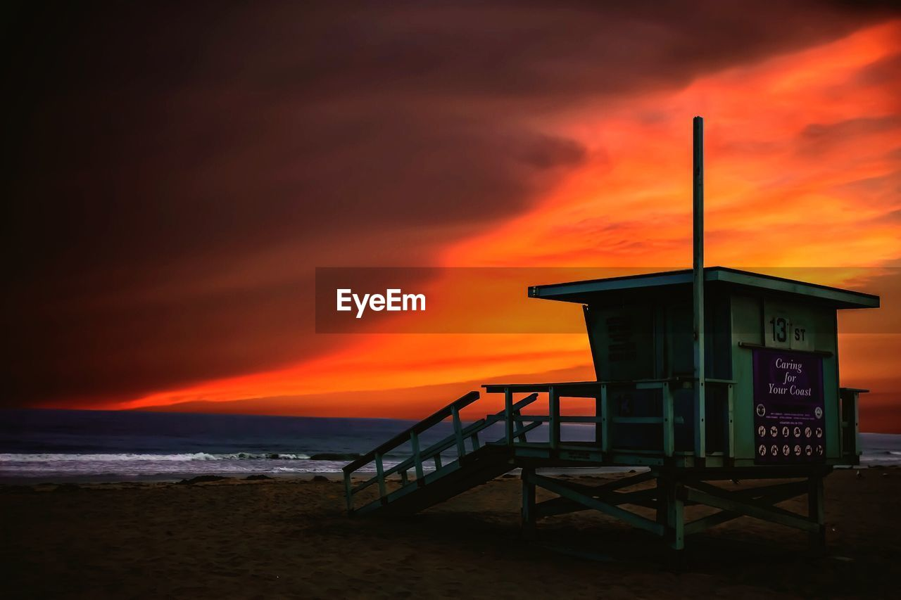 water, sunset, orange color, sky, sea, beach, land, architecture, lifeguard hut, built structure, beauty in nature, scenics - nature, nature, hut, cloud - sky, safety, horizon over water, man made structure, protection, no people, outdoors