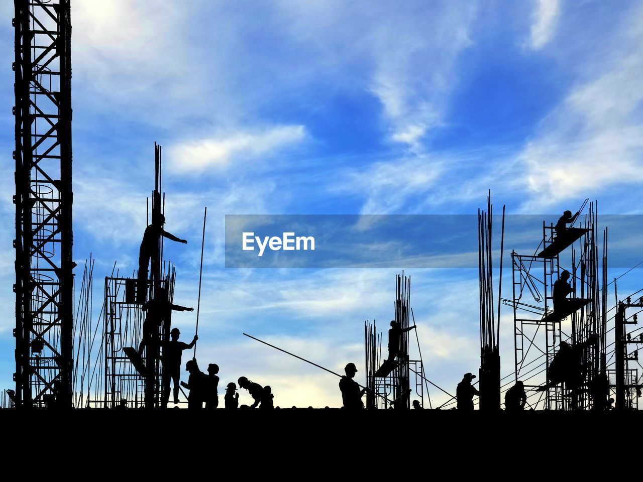 sky, cloud - sky, silhouette, group of people, nature, architecture, real people, outdoors, industry, low angle view, built structure, sunset, medium group of people, men, day, machinery, development, group, construction industry, lifestyles