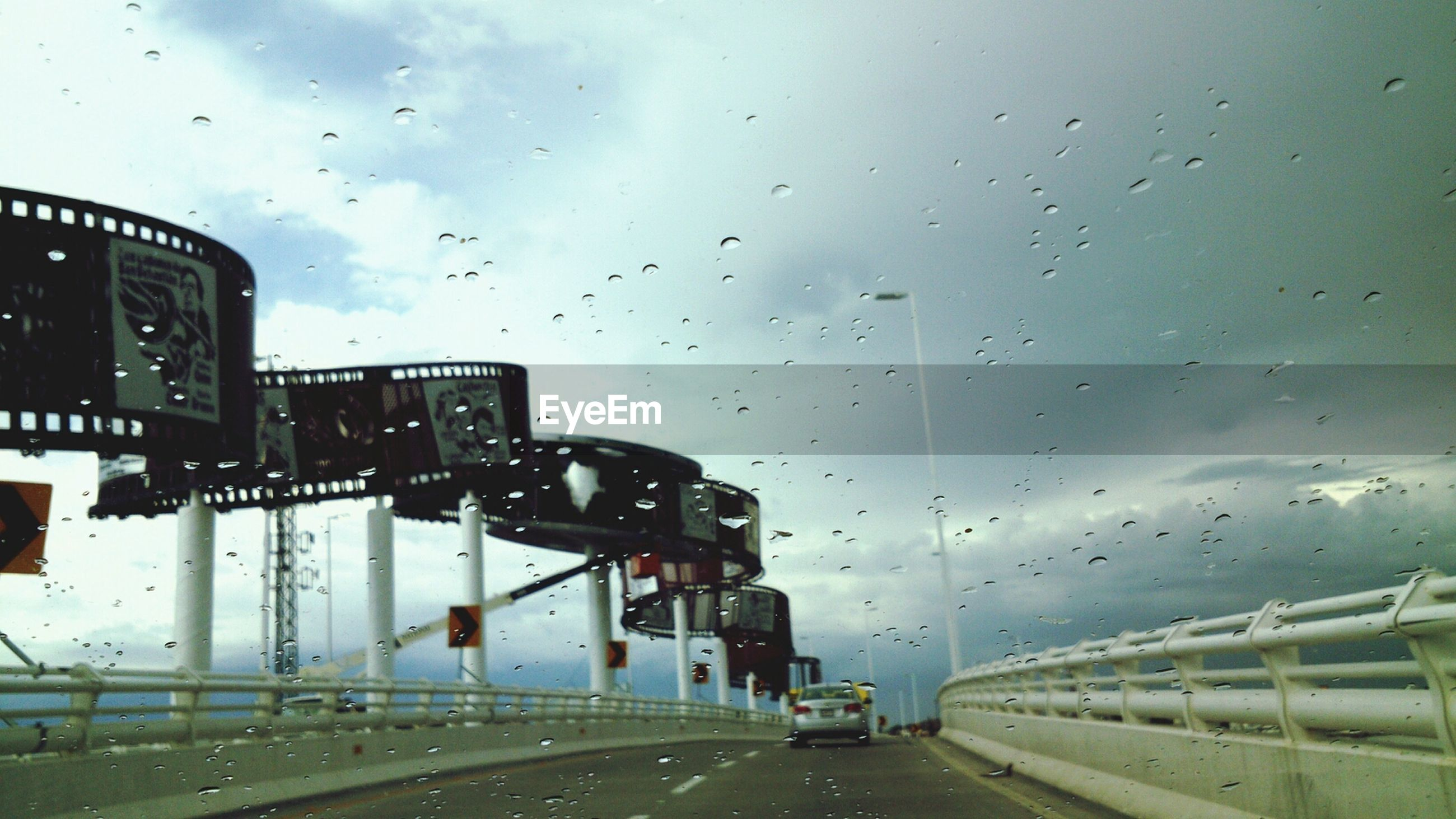 transportation, wet, drop, rain, sky, mode of transport, window, car, architecture, glass - material, built structure, transparent, building exterior, weather, land vehicle, road, indoors, city, cloud - sky, water