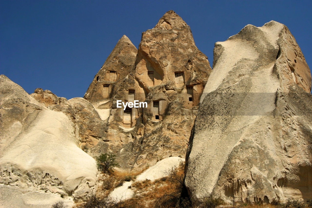 rock, sky, rock formation, solid, history, rock - object, architecture, the past, low angle view, clear sky, no people, nature, day, travel destinations, travel, built structure, mountain, geology, sunlight, ancient, outdoors, ancient civilization, eroded