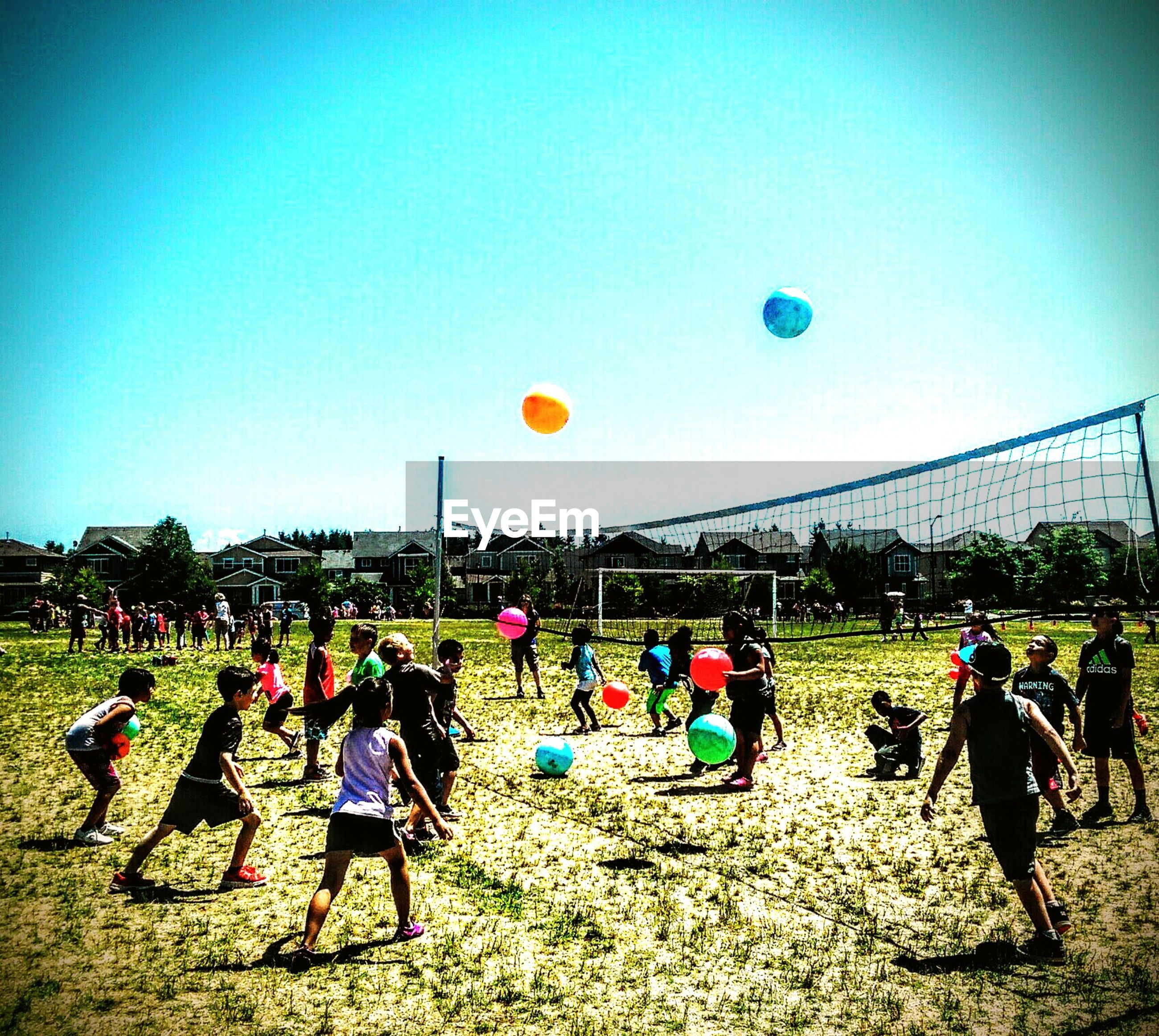 mid-air, playing, real people, large group of people, sport, ball, soccer, outdoors, skill, day, men, leisure activity, sky, playing field, clear sky, grass, nature, people, adult