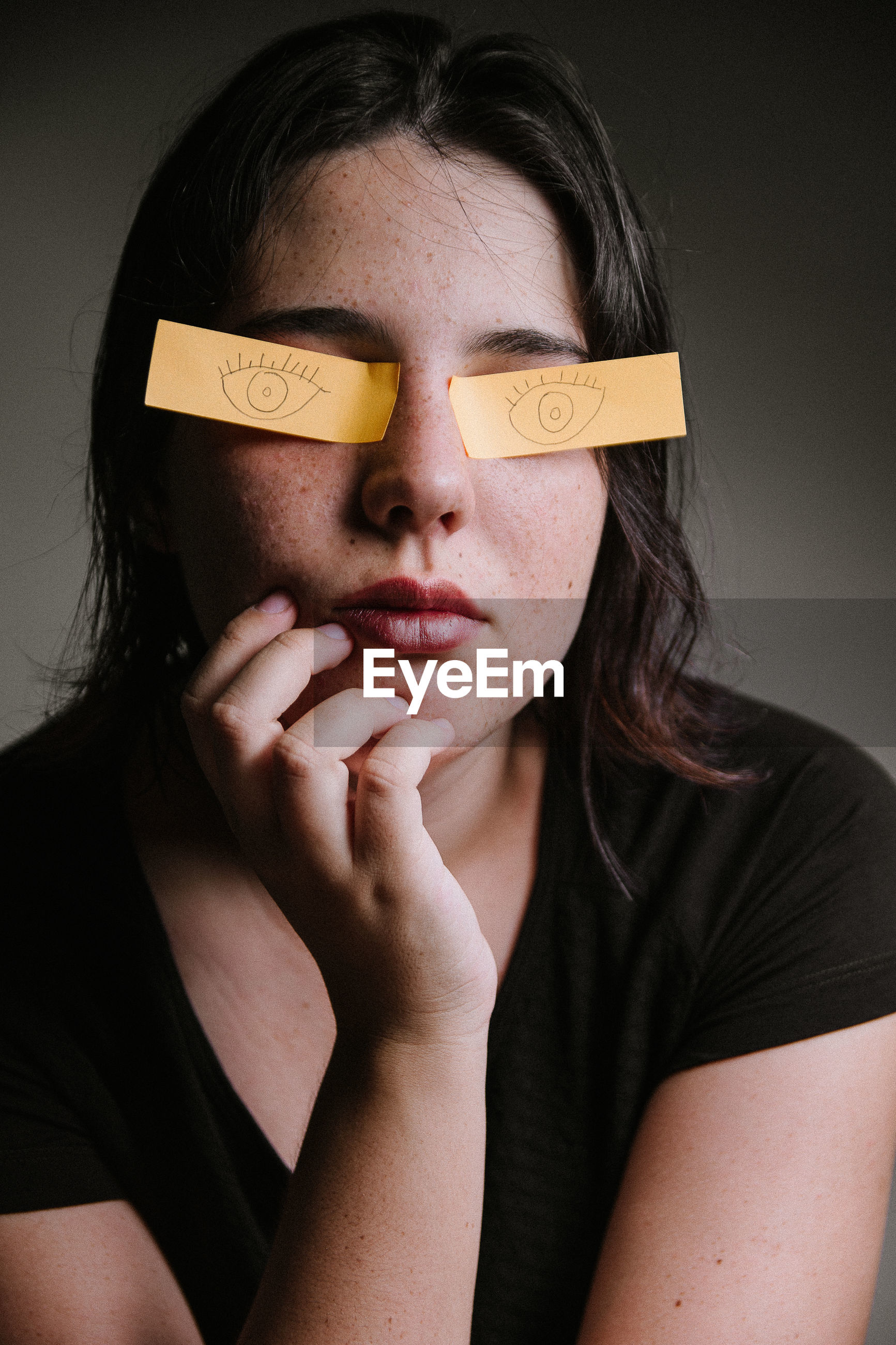 Young woman with eyes covered by papers against gray background