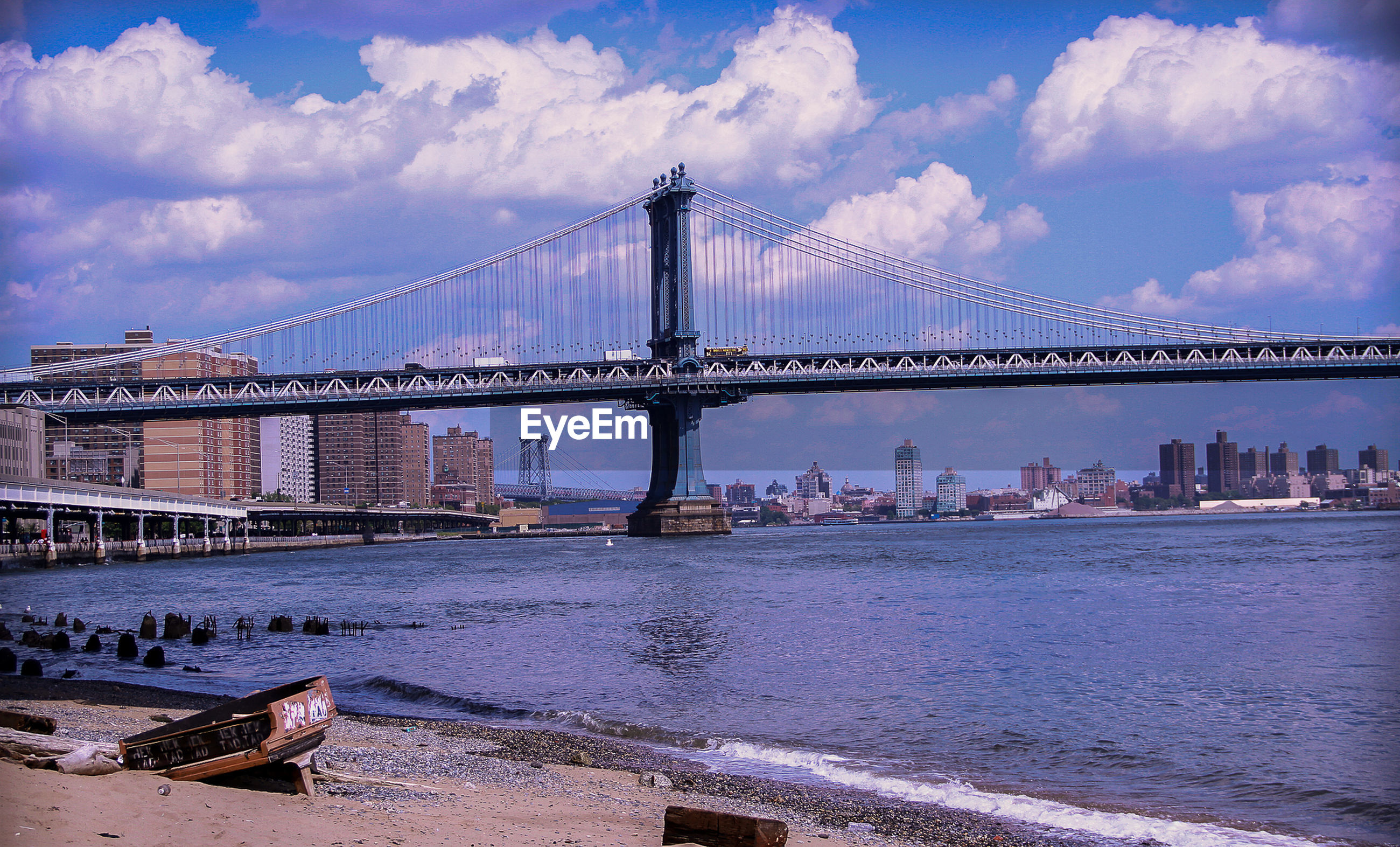 Old abandoned piano by manhattan bridge and river against cloudy sky in city