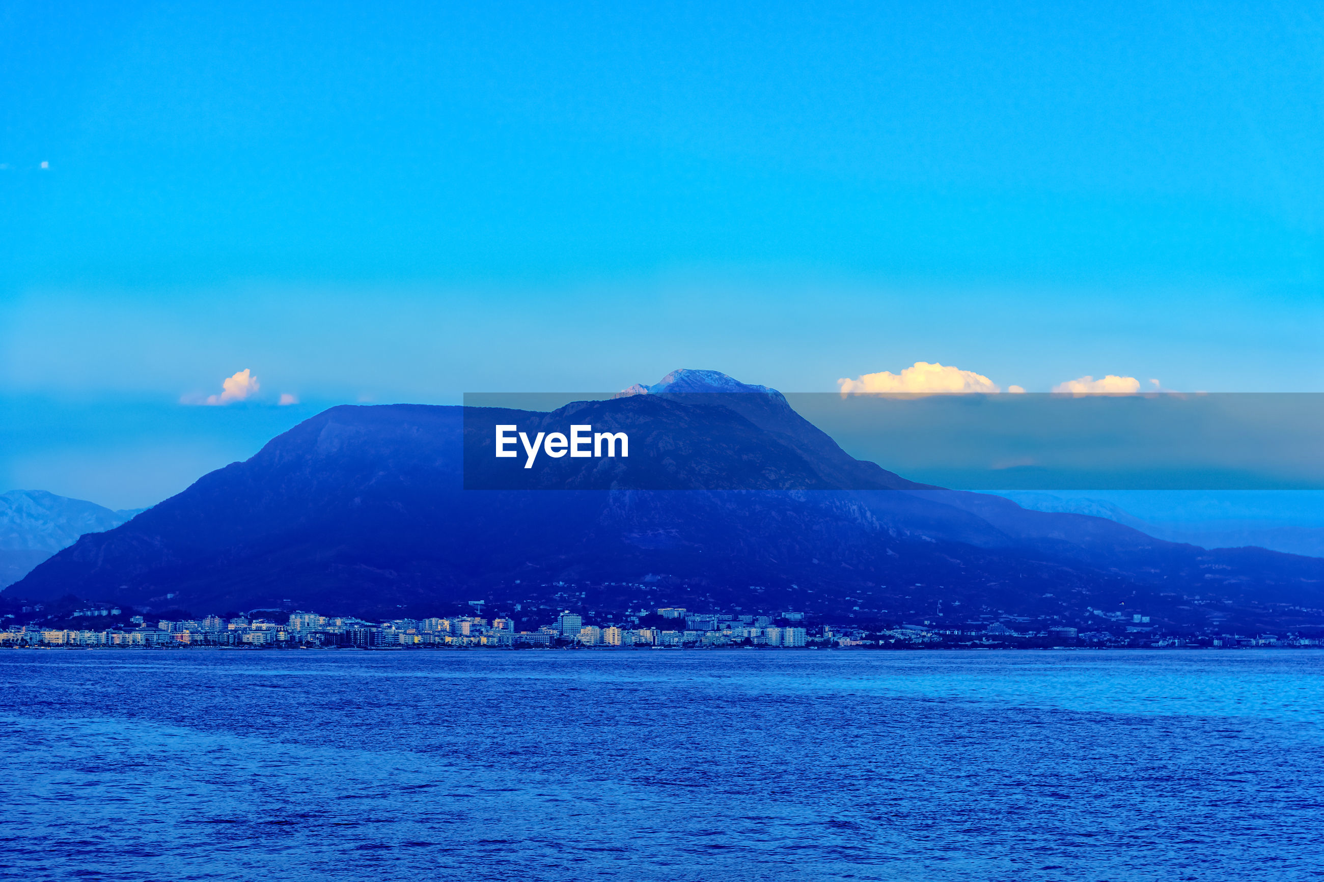 SCENIC VIEW OF SEA AGAINST MOUNTAIN RANGE