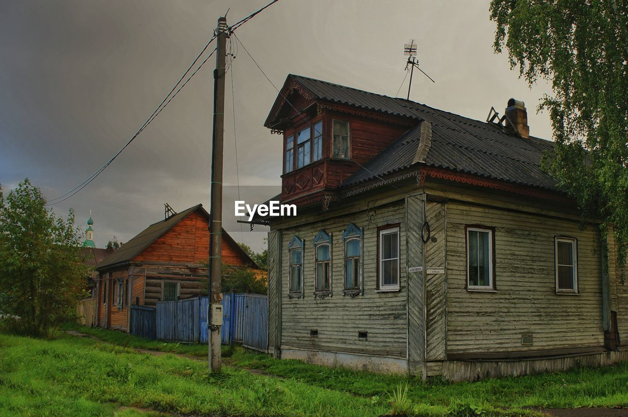HOUSE ON FIELD BY BUILDING AGAINST SKY