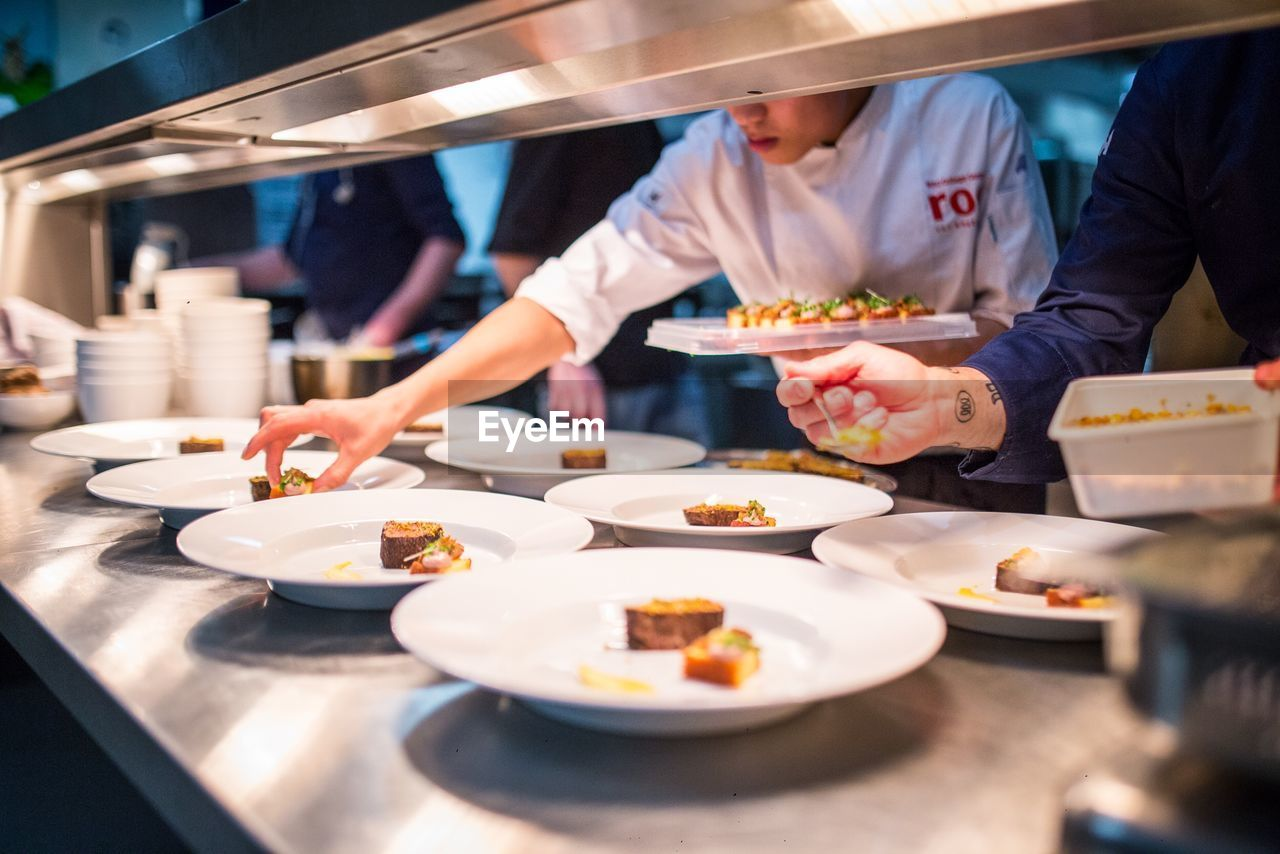 Midsection Of Chefs Serving Foods In Restaurant