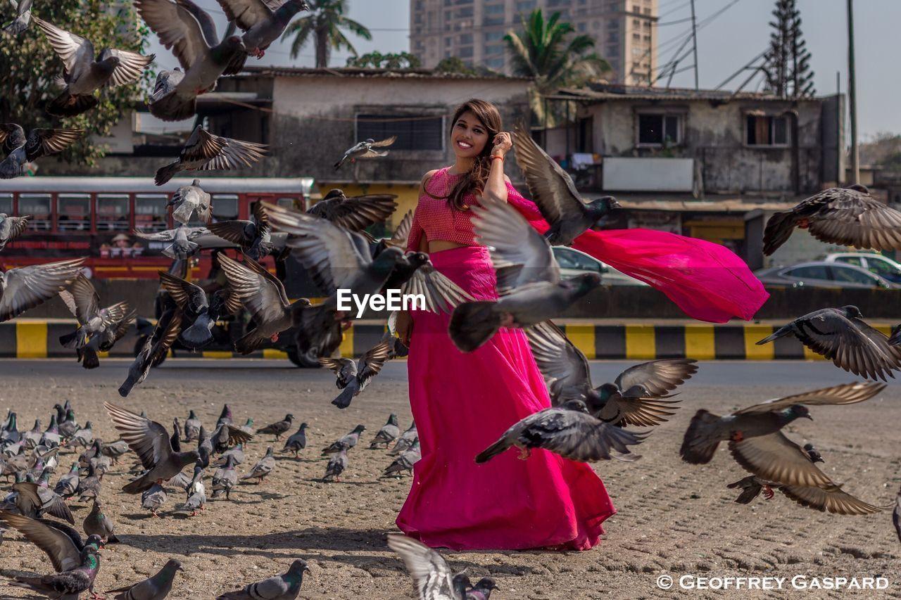 WOMAN FLYING BIRDS IN CITY