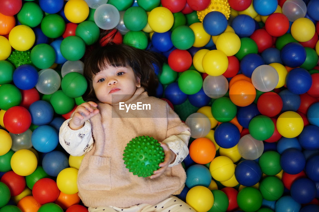 High angle view of cute baby girl looking away while lying on colorful balls