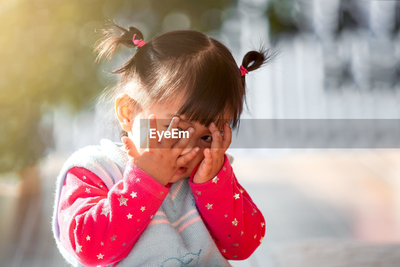Portrait of cute baby girl covering eyes against outdoors