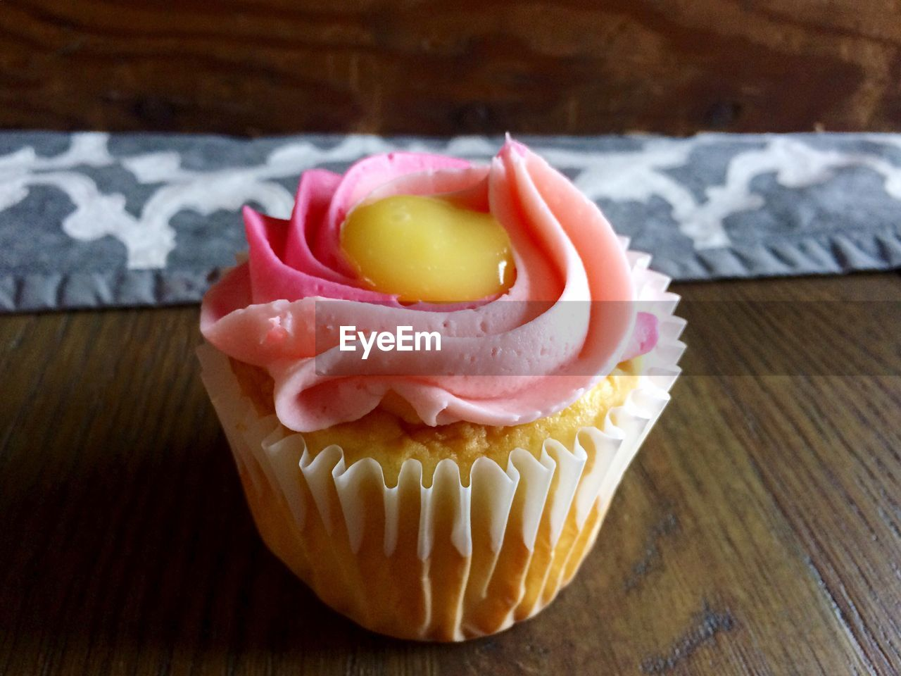 food, table, freshness, food and drink, indoors, still life, close-up, cupcake, no people, sweet food, cake, ready-to-eat, pink color, indulgence, focus on foreground, baked, sweet, dessert, wood - material, unhealthy eating, temptation, cupcake holder, snack