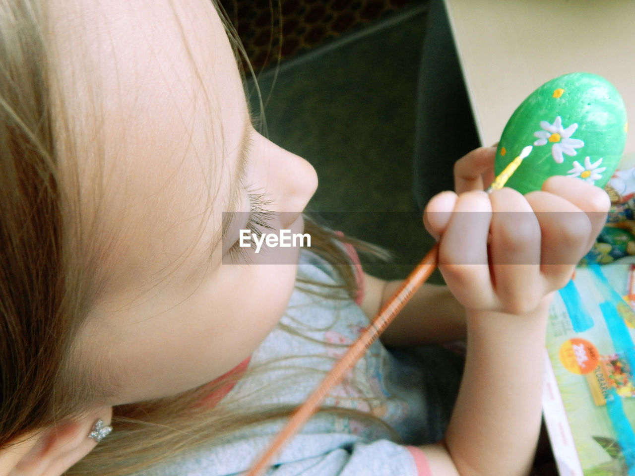 High Angle View Of Girl Painting On Easter Egg
