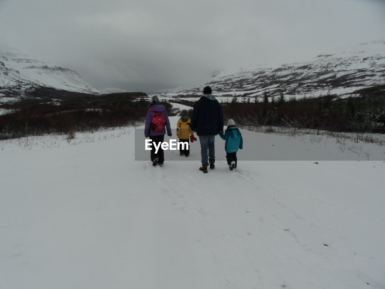 Rear View Of Family Walking On Snow Covered Mountain Against Sky