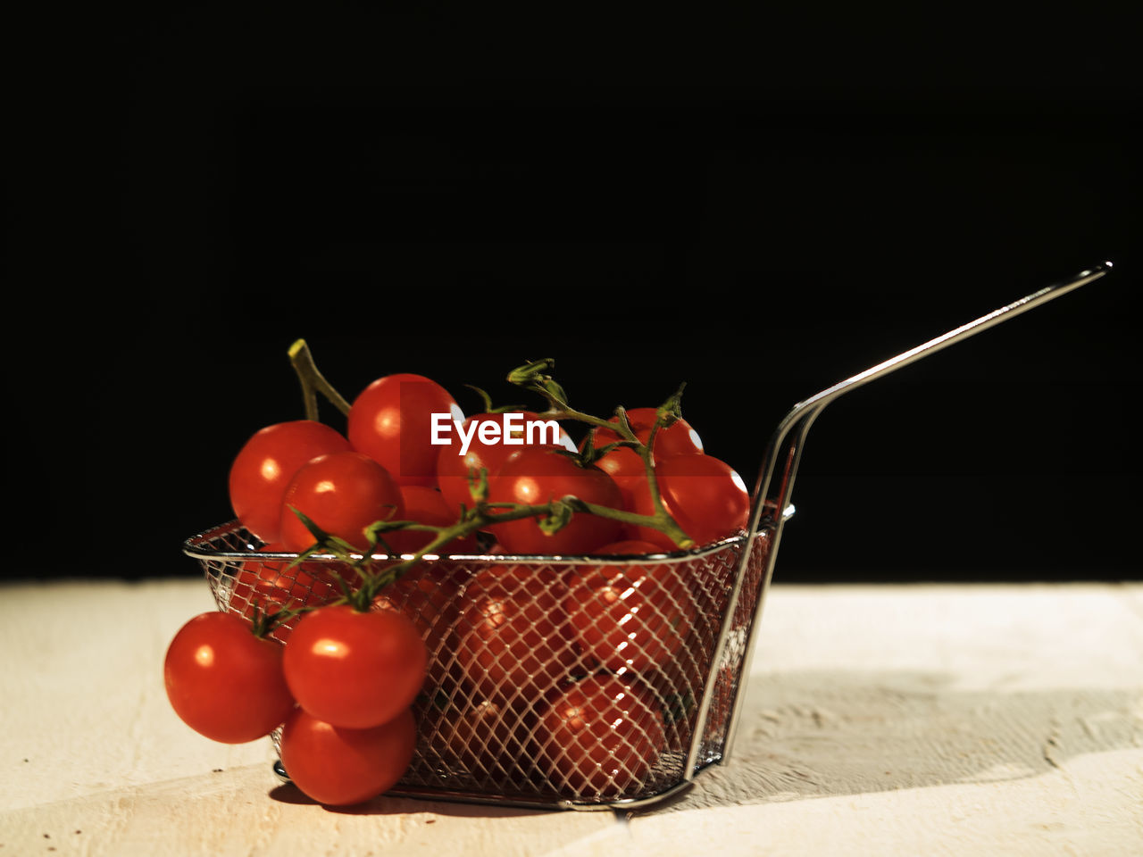 Cheery Tomatoes In Metallic Basket On Table Against Black Background