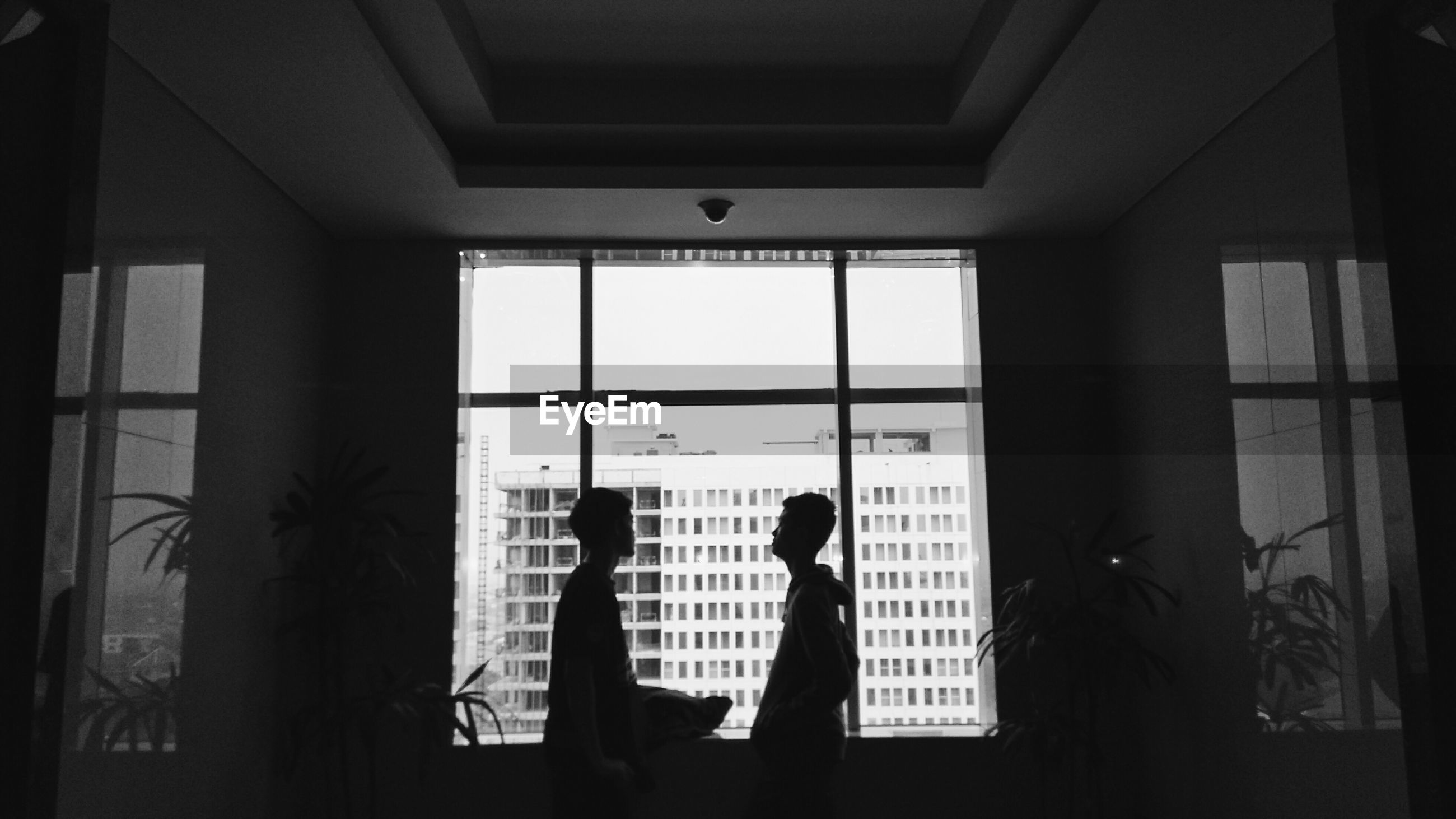 indoors, architecture, silhouette, window, built structure, men, lifestyles, glass - material, person, sunlight, walking, standing, shadow, building, day, building exterior, leisure activity, dark, transparent
