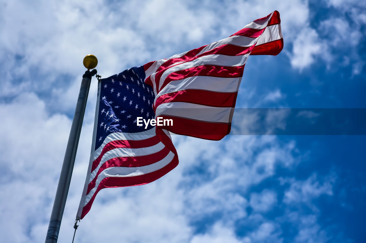 patriotism, flag, sky, low angle view, cloud - sky, nature, red, striped, no people, day, environment, wind, star shape, pole, shape, waving, blue, outdoors, freedom, national icon, independence