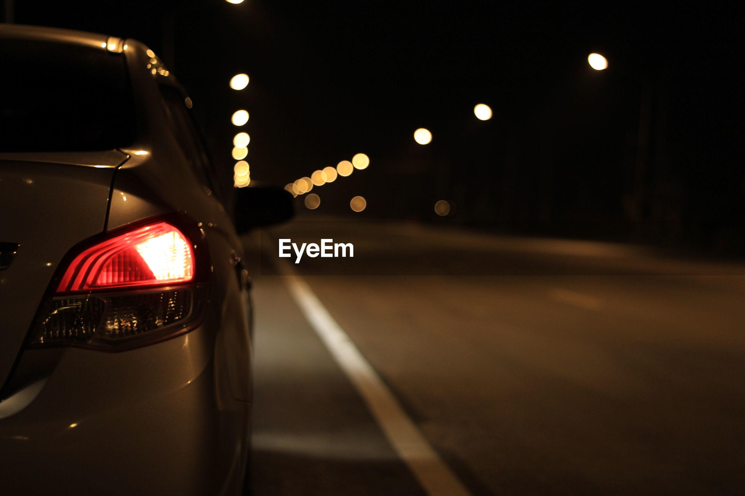 Close-up of illuminated car on road at night