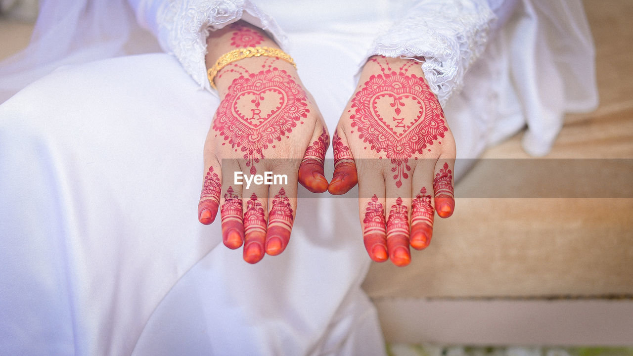 midsection, real people, human body part, one person, women, adult, lifestyles, indoors, clothing, focus on foreground, pattern, wedding, life events, human hand, hand, body part, celebration, white color, design, floral pattern, human limb
