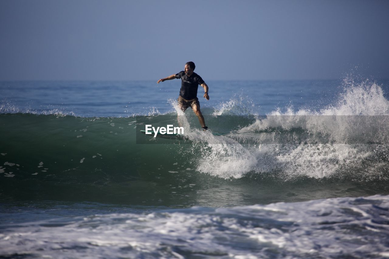 sea, water, sport, motion, real people, leisure activity, one person, waterfront, lifestyles, wave, surfing, aquatic sport, sky, horizon over water, splashing, beauty in nature, men, adventure, skill, outdoors, power in nature