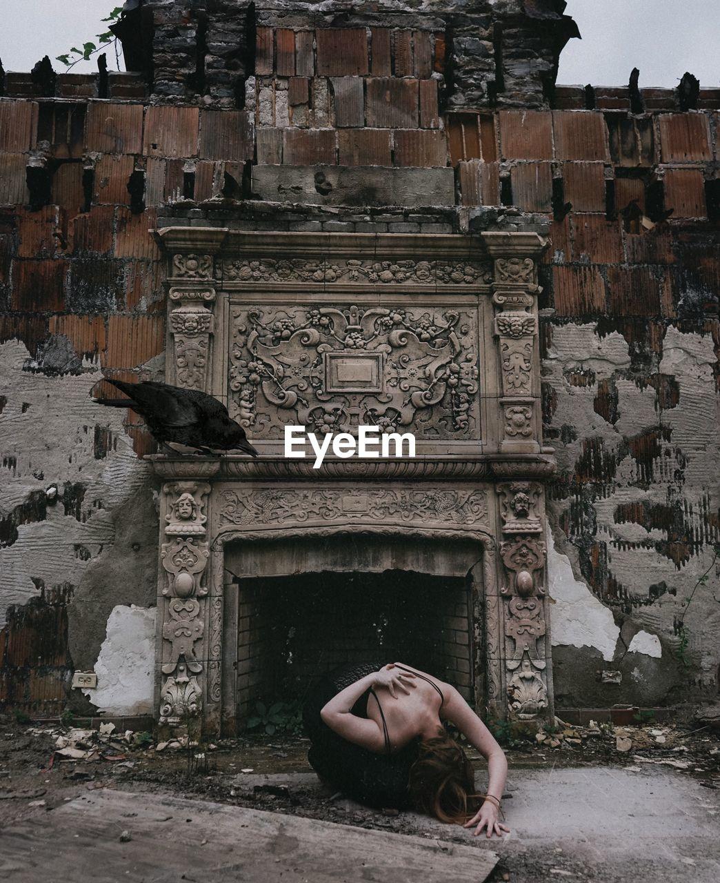 Woman bending against abandoned building