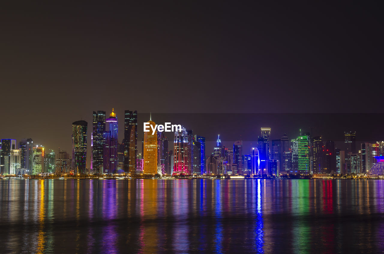 building exterior, architecture, water, illuminated, built structure, night, waterfront, city, building, urban skyline, sky, office building exterior, cityscape, reflection, landscape, skyscraper, modern, tall - high, no people, outdoors, financial district, nightlife, luminosity