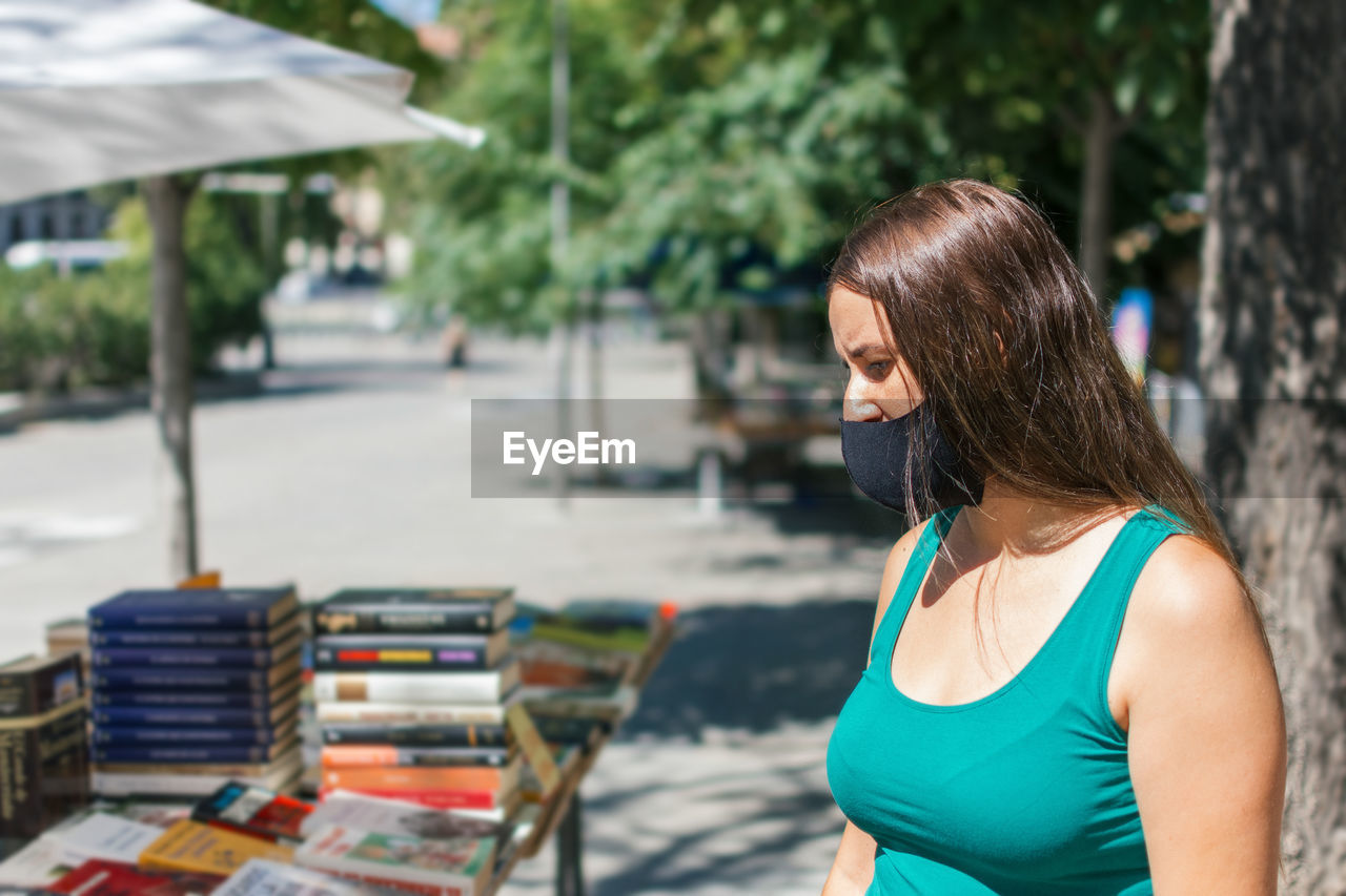 Young woman wearing mask standing outdoors